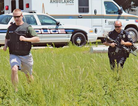 Drug Task Force Detective Josh Talbott, left, and Jonesboro Police Department Patrolman First Class Duane Busby run across a field adjacent to Moore Road while responding to a Saturday, May 3, 2014 shooting in Jonesboro