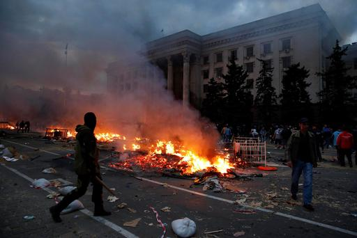 A protester walks past a burning pro-Russian tent camp near the trade union building in Odessa May 2, 2014