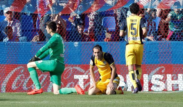 Atletico Madrid's goalkeeper Thibaut Courtois from Belgium, left, and Diego Godin from Uruguay, center, stay on the ground after Levante scored a second goal