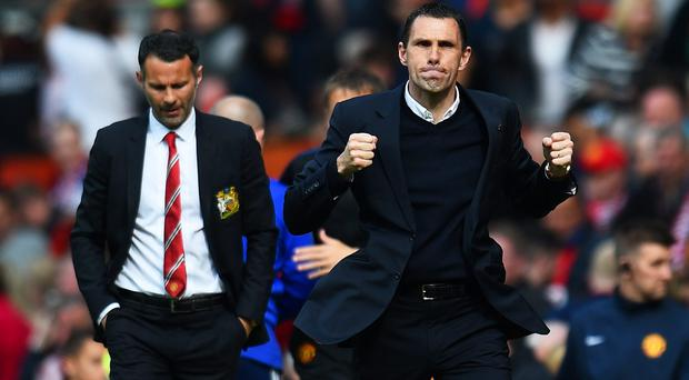 Delighted Sunderland manager Gustavo Poyet celebrates alongside a disappointed Ryan Giggs after his team virtually secured their Premier League safety with victory