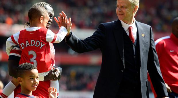 Arsenal manager Arsene Wenger greets Bacary Sagna's children as they walk around the pitch after their victory over West Bromwich Albion at the Emirates stadium