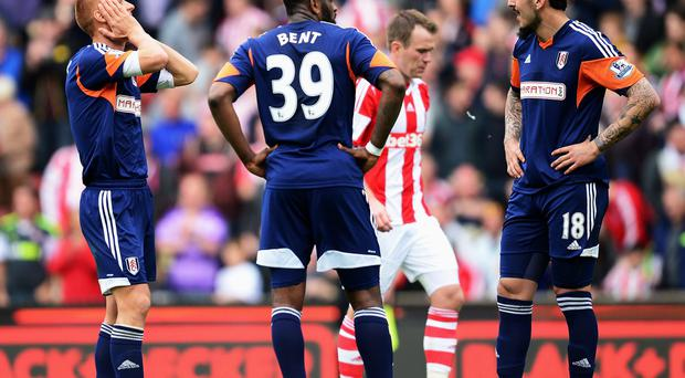 (L-R) Steve Sidwell, Darren Bent and Konstantinos Mitroglou of Fulham react as their side concedes a third goal during the Barclays Premier League match between Stoke City and Fulham at the Britannia Stadium in Stoke on Trent, England. (Photo by Jamie McDonald/Getty Images)