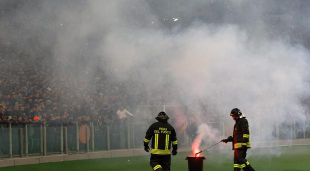 Firefighters remove a flare prior to the start of Italian Cup final match between Fiorentina and Napoli in Rome's Olympic stadium