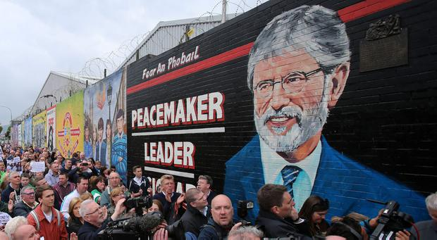 Nationalists attend the unveiling of a mural in honour of Gerry Adams in the Falls Road, Belfast