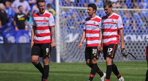 Doncaster players Chris Brown, Enda Stevens and Gabriel Tamas look dejected after the defeat to Leicester City at the weekend.