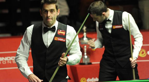Ronnie O'Sullivan leaves the arena as Mark Selby celebrates winning the final frame of the afternoon session of the Dafabet World Snooker Championships at The Crucible, Sheffield