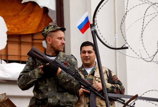 Armed pro-Russian activists stand guard at the entrance of the seized regional government headquarters in Luhansk, eastern Ukraine. Four Ukrainian paramilitary police were killed in fighting on Monday with pro-Russian separatists near the rebel stronghold of Slaviansk, the Interior Ministry said, in renewed violence Kiev is struggling to stop across the east. Reuters