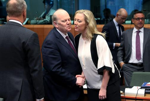 Ireland's Finance Minister Michael Noonan greets his Finnish counterpart Jutta Urpilainen during a Eurozone finance ministers meeting in Brussels