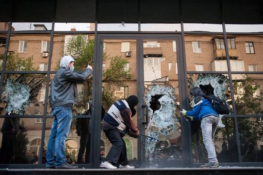 Pro-Russian activists brake the glass of the offices of Industrial Union of Donbass Corporation in Donetsk, eastern Ukraine