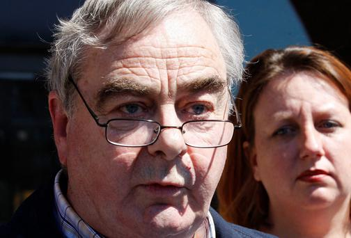 Journalist Ed Moloney (L) addresses reporters as Carrie Twomey, wife of former IRA member Anthony McIntyre, watches on