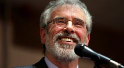 Sinn Fein president Gerry Adams smiles as he delivers a speech at an election rally