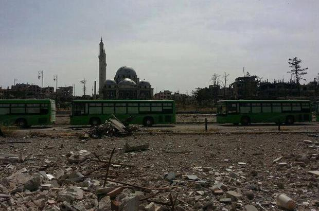 A picture uploaded on the Internet showed two green buses driving through the dusty ruins of central Homs towards a collection point for the withdrawing rebel fighters.