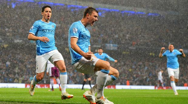 Edin Dzeko of Manchester City celebrates scoring the opening goal with Samir Nasri (L) during the Barclays Premier League match between Manchester City and Aston Villa at Etihad Stadium. (Photo by Michael Regan/Getty Images)