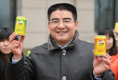 BEIJING, CHINA - JANUARY 30: (CHINA OUT) Chen Guangbiao (R), Chairman of Jiangsu Huangpu Recycling Resources Co., Ltd, presents his company's product canned fresh air at Beijing Financial Street on January 30, 2013 in Beijing, China. Chen is known for his high-profile charity activities. Heavy fog has been lingering in central and eastern China since Tuesday afternoon, disturbing the traffic and worsening air pollution. (Photo by ChinaFotoPress/ChinaFotoPress via Getty Images)