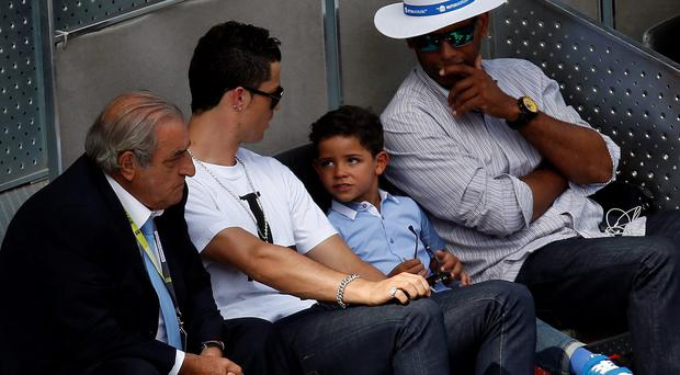 Real Madrid's Cristiano Ronaldo (2nd L) and his son Cristiano Ronaldo Jr attend the Nadal-Nieminen match at the Madrid Open tennis tournament May 8, 2014.