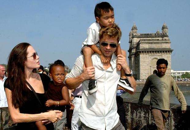 US actor Angelina Jolie (L) holds daughter Zahara as husband and actor Brad Pitt (C) carries son Maddox during a stroll on the seafront promenade at the historic Gateway of India, (R) outside their hotel in Mumbai, 12 November 2006.