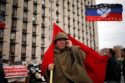 A man holds a Soviet flag during celebrations to mark Victory Day outside a regional government building in Donetsk, eastern Ukraine May 9, 2014. Russian President Vladimir Putin praised the Soviet role in defeating fascism on Friday, the anniversary of the World War Two victory over Nazi Germany, and said those who defeated fascism must never be betrayed. REUTERS/Marko Djurica (UKRAINE - Tags: ANNIVERSARY POLITICS CONFLICT MILITARY)