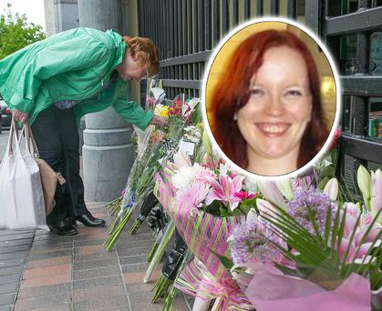 A woman reads floral tributes outside the shopping centre in Kilkenny where Mairead Moran (inset) was killed. Photo: Pat Moore