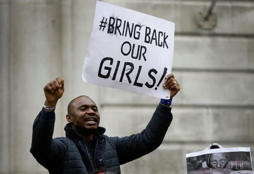 A demonstrator holds a banner, during a protest about the kidnapping of girls in Nigeria, near the Nigerian High Commission in London. (AP Photo/Kirsty Wigglesworth)
