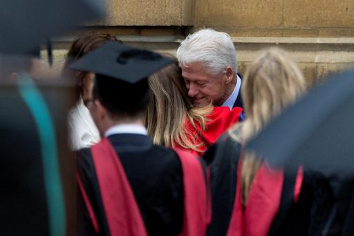 Former U.S. President Bill Clinton hugs his daughter Chelsea after attending her Oxford University graduation ceremony with his wife former Secretary of State Hillary Rodham Clinton. (AP Photo/Matt Dunham)