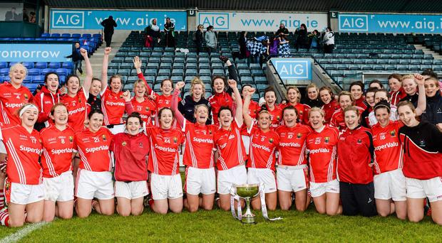The Cork team celebrate victory over Dublin with the cup