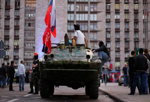 A pro-Russia rebel sits on top of an armoured vehicle outside a regional government building in Donetsk, eastern Ukraine