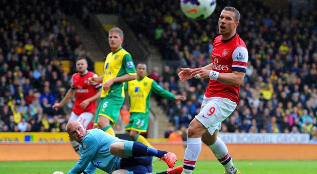 John Ruddy of Norwich City looks on as Lukas Podolski of Arsenal reacts during the Barclays Premier League at Carrow Road.