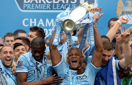 Manchester City's Vincent Kompany lifts the Barclays Premier League trophy following the Barclays Premier League match at the Etihad Stadium.