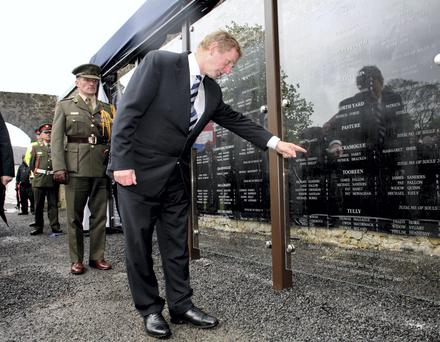 Taoiseach Enda Kenny reads names of famine victims written on a glass wall in Strokestown Park House, Co Roscommon. Photo Brian Farrell