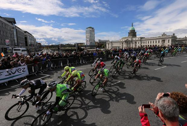 The peloton crosses the Matt Talbot Bridge, with Customs House in the background, during the closing stages of yesterday's Stage 3 of the Giro D'Italia in Dublin