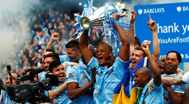 Manchester City's captain Vincent Kompany (C) lifts the Premier League trophy after yesterday's win over West Ham United at the Etihad Stadium