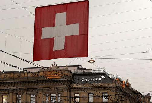 A national flag of Switzerland flies in front of the headquarters of Swiss bank Credit Suisse in Zurich