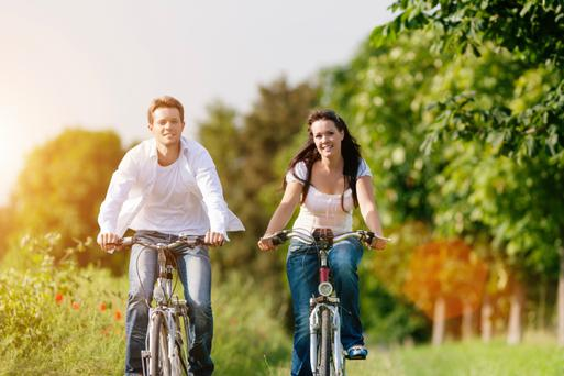 young couple cycling with bicycle in summer