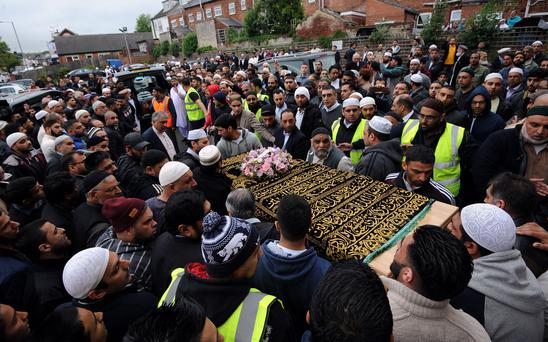 Mourners gather as a coffin of one of the five family members who died in a house fire is carried away after a funeral service at the Masjid Mosque, Sheffield