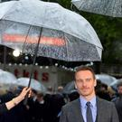 Irish-German actor Michael Fassbender is shielded from the rain as he arrives for the British premiere of 'X-Men: Days of Future Past' at Leicester Square in London May 12, 2014. REUTERS/Toby Melville (BRITAIN - Tags: ENTERTAINMENT)