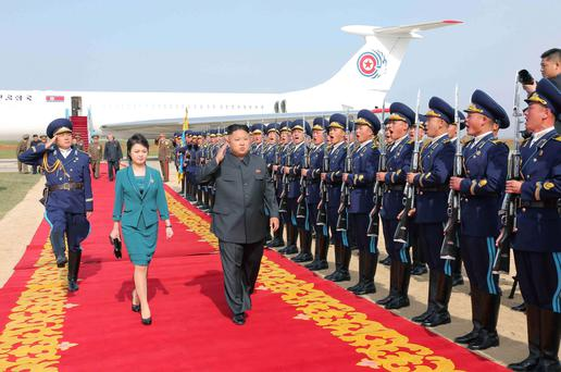 North Korean leader Kim Jong Un salutes as he and his wife Ri Sol Ju walk past the guard of honour upon arriving for the 2014 Combat Flight Contest