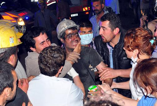 A rescued miner surrounded by relatives, medics and other miners cries after being rescued from a coal mine he was in trapped in Soma, a district in Turkey's western province of Manisa, May 13, 2014.