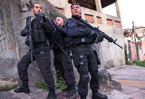 Officers from the CORE police special forces hold their weapons during an operation to search for fugitives in the Complexo do Alemao pacified community, or 'favela' on May 13, 2014 in Rio de Janeiro, Brazil. Ahead of the 2014 FIFA World Cup, Rio has seen an uptick in violence in its pacified slums.