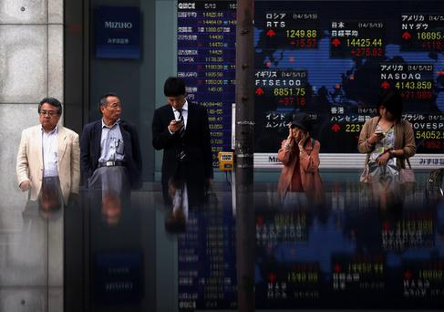 Pedestrians standing in front of an electronic board showing the various countries' stock market indices