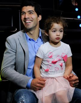 Luis Suarez of Liverpool sits with his daughter Delfina during the presentation as new Ambassador for 888poker