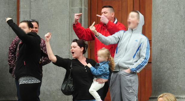 Members of the public gesture at the accused