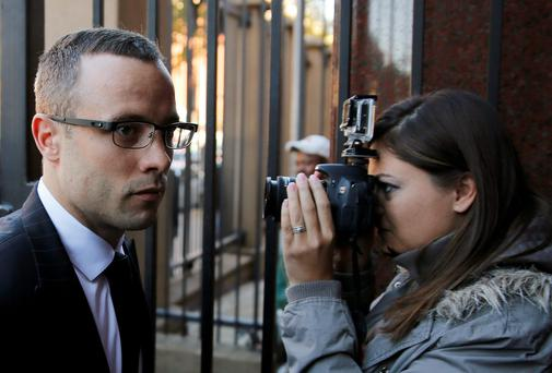 A photographer snaps Olympic and Paralympic track star Oscar Pistorius as he arrives at North Gauteng High Court in Pretoria. Pistorius's trial has been paused as the court awaits the results of a 30-day psychiatric evaluation. Photo: REUTERS/Siphiwe Sibeko