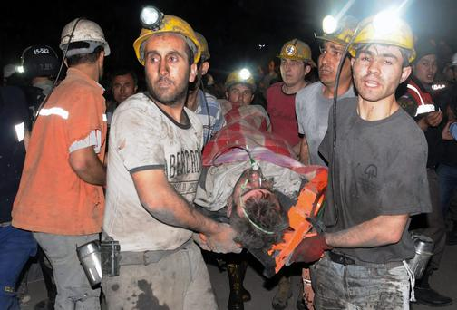 Miners carry a rescued man after the coal-mine explosion and fire killed at least 245 people and left up to 200 workers trapped underground in Soma, western Turkey. Photo: AP Photo/Depo Photos
