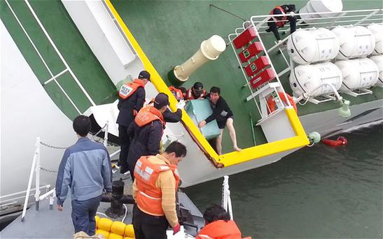 Captain Lee Joon-seok, centre right wearing a sweater and underpants, is rescued from the Sewol Photo: KOREA COAST GUARD/AFP