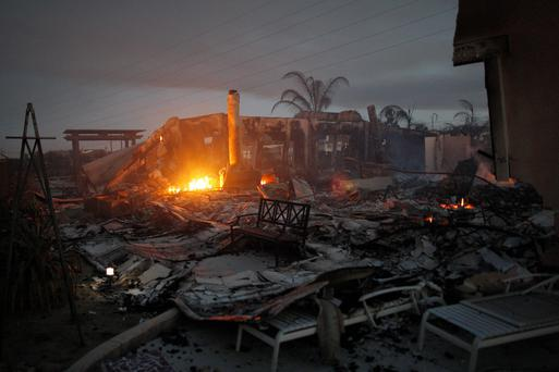 The ruins of a home smoulder in the night after it was destroyed in the Poinsettia fire, one of nine wildfires fueled by wind and record temperatures that erupted in San Diego County throughout the day, on May 14, 2014 in Carlsbad, California