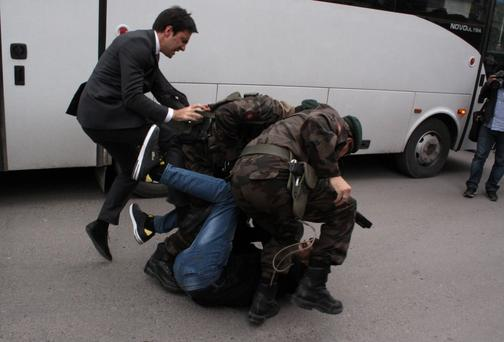 In this photo taken Wednesday, May 14, 2014 a person identified by Turkish media as Yusuf Yerkel, advisor to Turkish Prime Minister Recep Tayyip Erdogan, kicks a protester already held by special forces police members during Erdogan's visiting Soma, Turkey