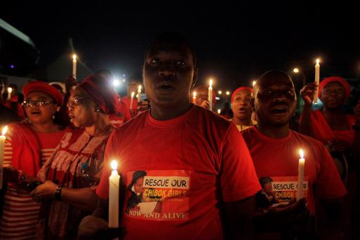 People hold candle light during a vigil to mark one month after the girls of government secondary school Chibok were kidnapped, in Abuja, Nigeria. (AP Photo/Sunday Alamba)