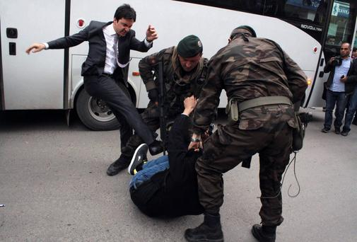 Yusuf Yerkel, advisor to Turkish prime minister Recep Tayyip Erdogan, kicks a protester already held by special forces police members during Mr Erdogan's visit to the scene of the mining tragedy in Soma, Turkey