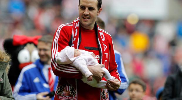 Sunderland's John O'Shea holds his baby as he walks around the pitch after the final game of the season
