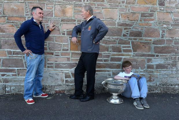 Andrew O'Brien, aged 13 from Bray, takes charge of the Sam Maguire Cup at Keel Community Centre as Micheal O Muircheartaigh chats to former Carlow player John Nevan